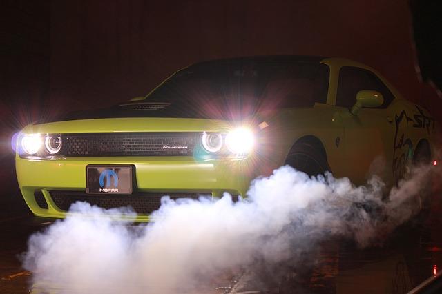 žluté auto, rozsvícená světla, kouř